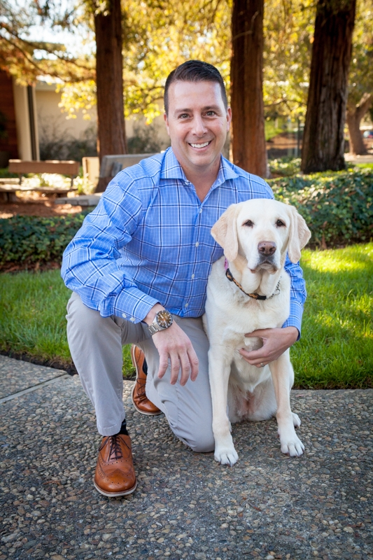 Dan L'Abbe kneeling next to a Lab/Golden dog.