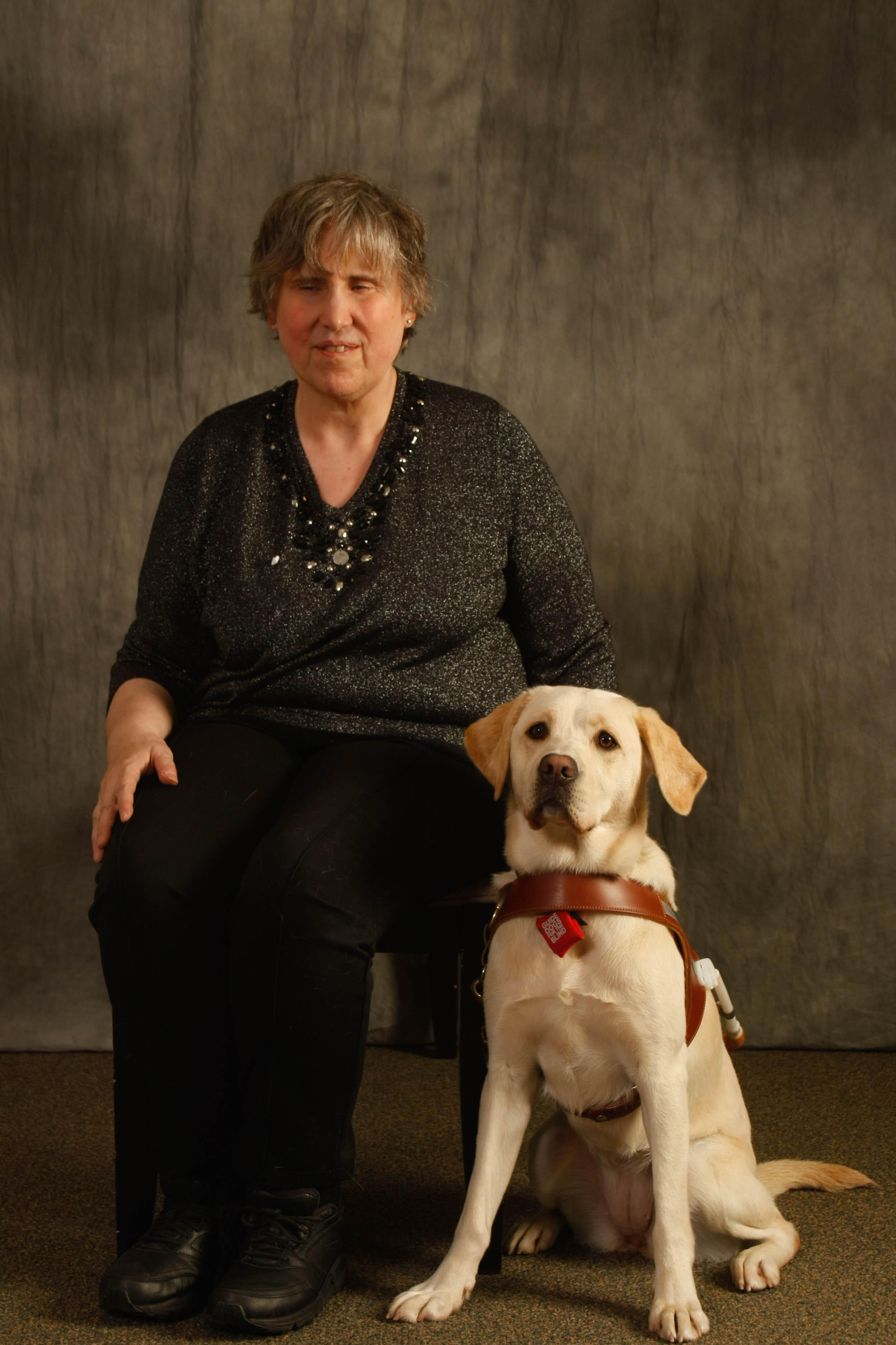 Class photo of Deb seated beside yellow Lab guide dogs Praline at their GDB graduation.