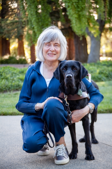 A portrait of Joan Robinson kneeling next to her black Lab guide dog, Forester.