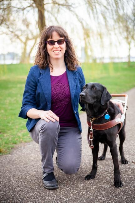 A portrait of Leanne Bremner kneeling next to her black Lab guide dog, Eva.