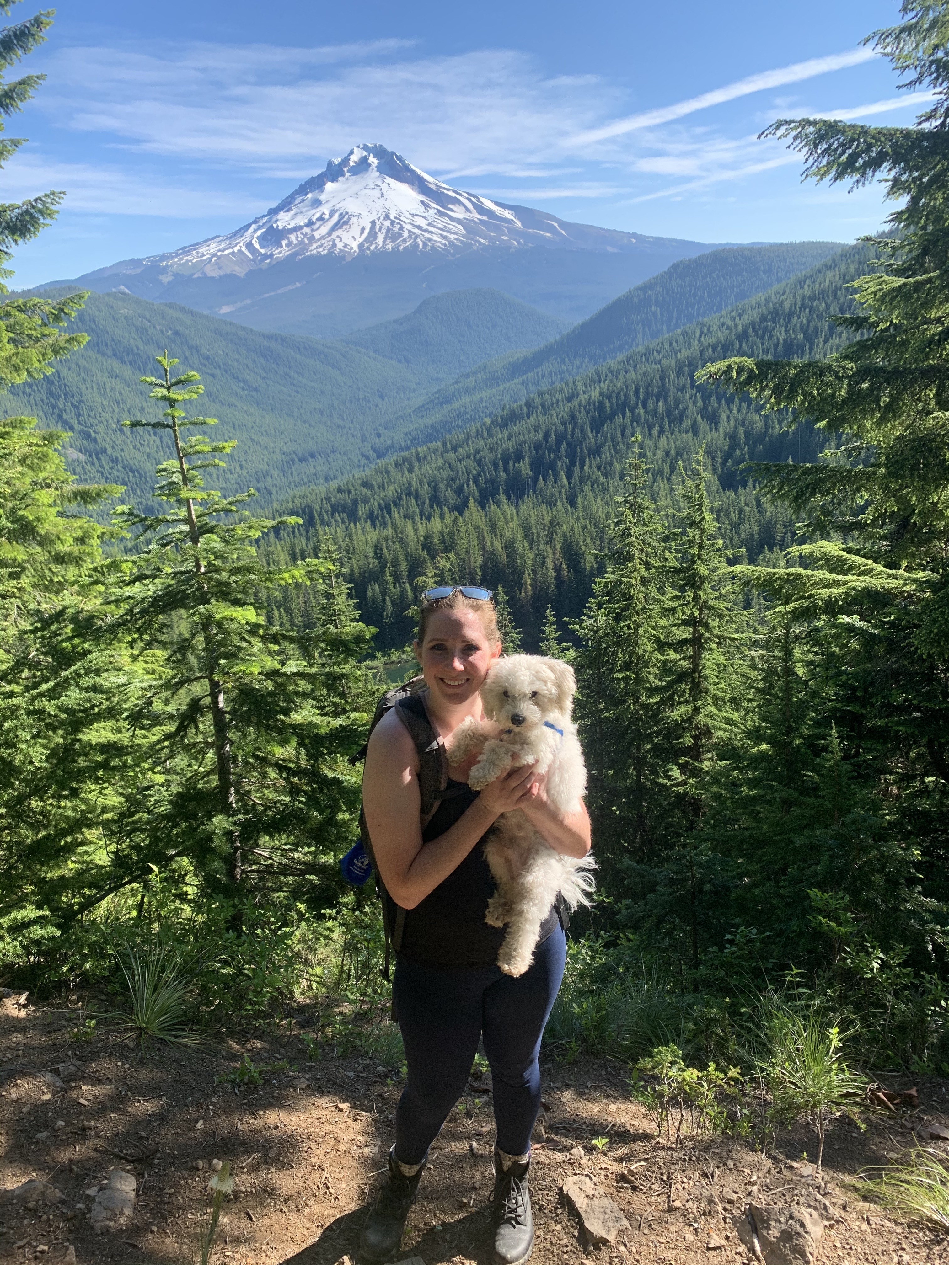 Kadi smiles for a photo op on a hiking trail with stunning mountain vistas. Kadi is holding a small white dog in her arms.
