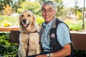 GDB grad Bruce Gilmour sits on a bench with his golden retriever guide dog Marley