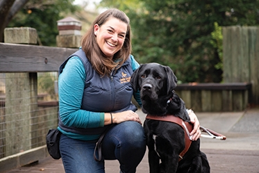Guide Dog Mobility Instructor Gina Paolini with a black Lab guide dog in harness.