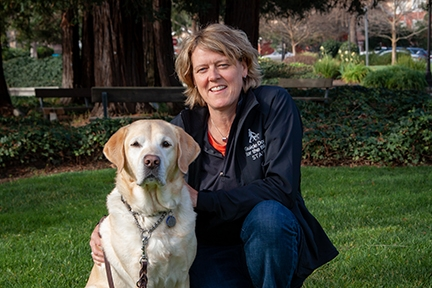 Dr. Kate Kuzminski kneeling next to a yellow Lab on a green grass with trees in the background.