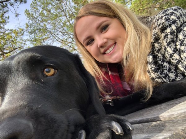 Selfie shot of Beth Deer smiling into the camera with her black Lab guide dog, Patronus, by her side.