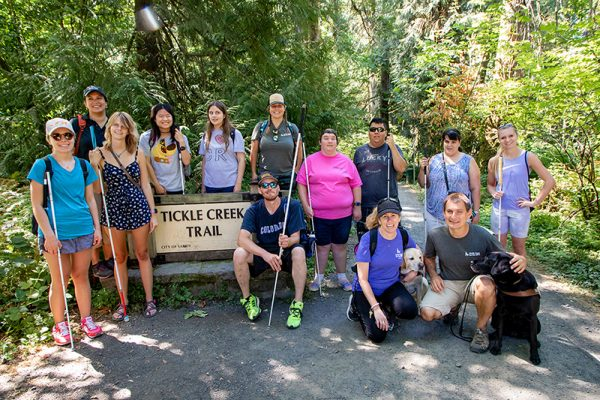 A group photo of campers at Camp GDB at the trailhead of a hiking path.
