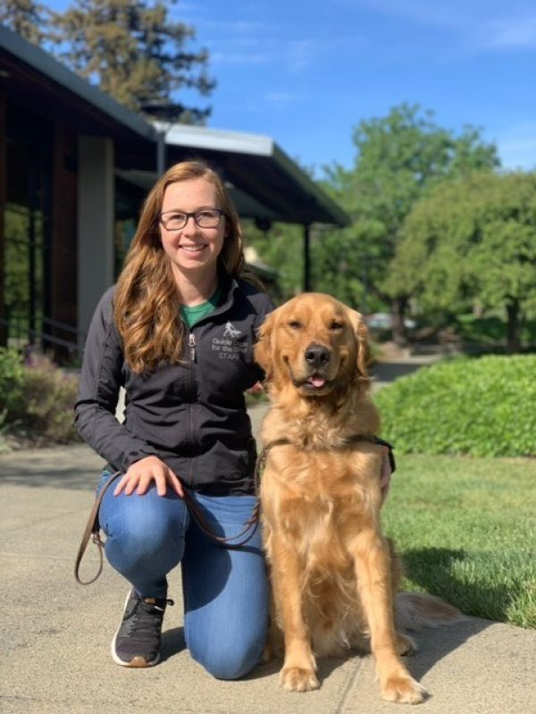 Emily Crisp kneeling next to a Golden Retriever guide dog