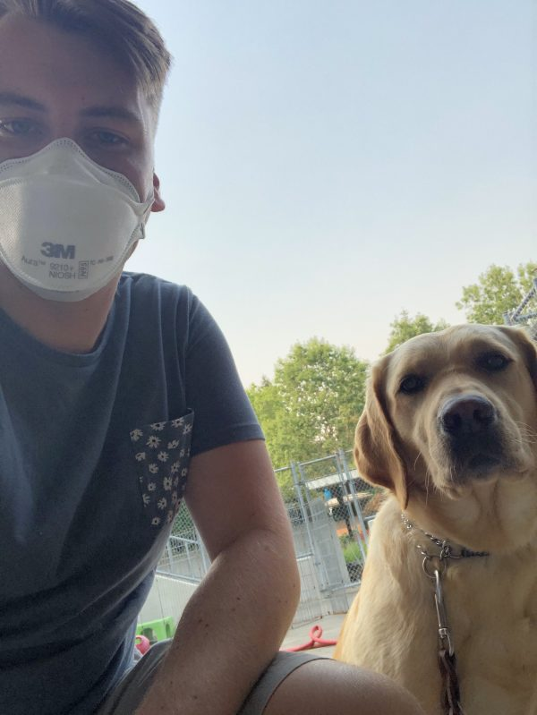 GDB Trainer Joey Float kneels beside a yellow Lab guide dog with smokey skies behind them. Joey wears an N95 mask to protect himself from smoke inhalation.