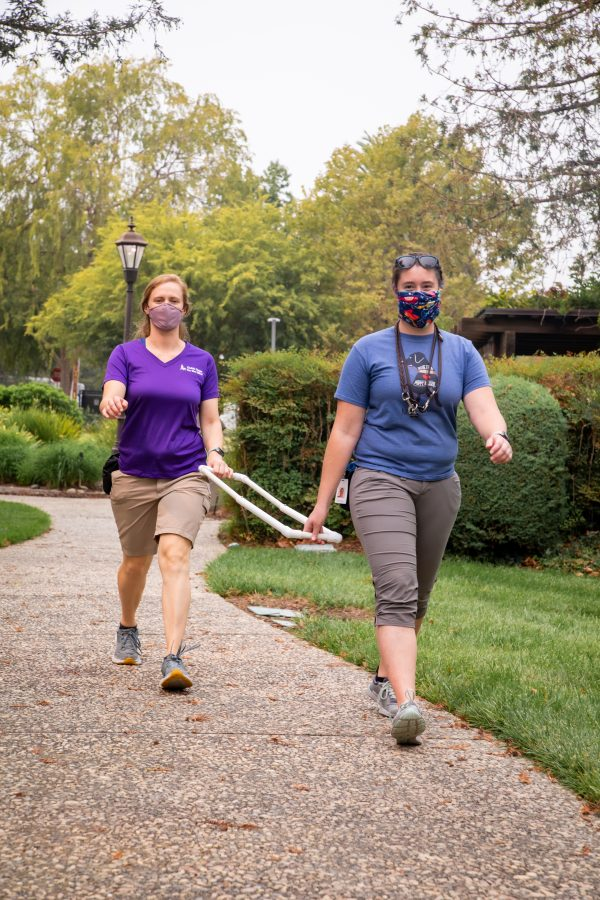Two members of the GDB Training staff demonstrate how they are able to use extended training tools during training in order to maintain required social distancing.