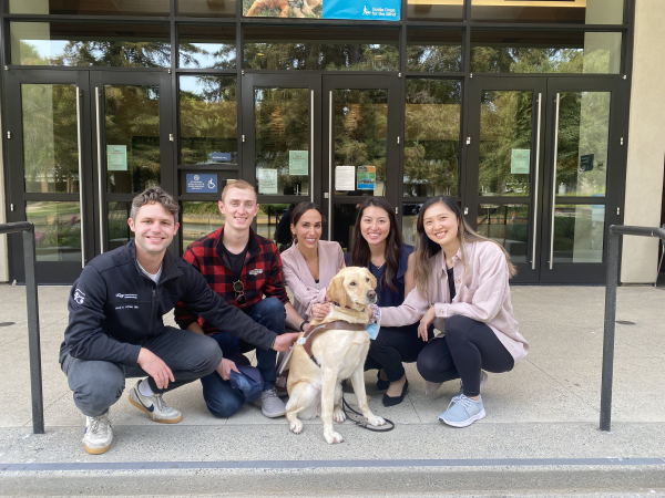 Five Ophthalmology residents kneel together on the GDB campus with a yellow Lab guide dog in harness.