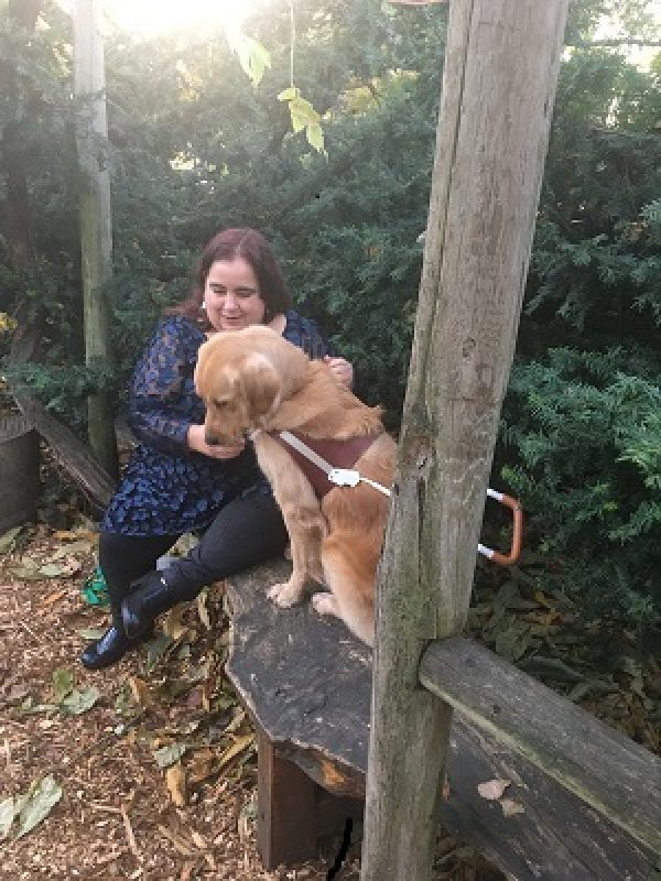 Maia Scott and her guide dog Gleam sit on a bench in the woods