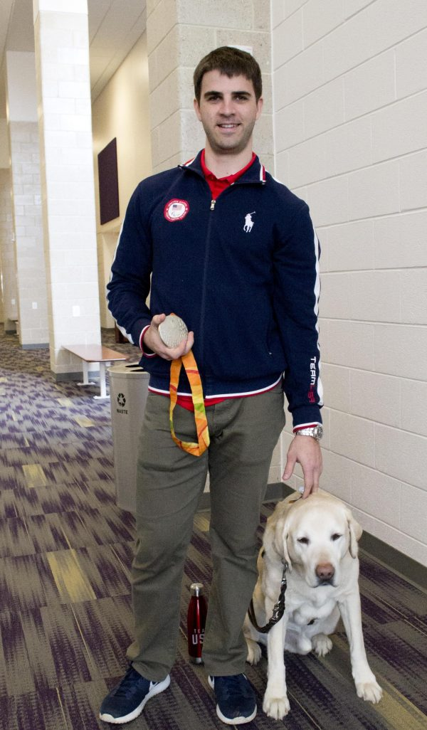 Paralympian Matt Simpson poses with his silver medal and his yellow Lab guide dog, Lacrosse.