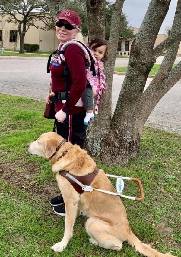 Melissa Padron with her guide dog Cameo. Melissa carries her young daughter in a baby carrier on her back.