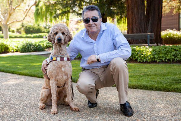 Man kneeling beside a guide dog in harness.