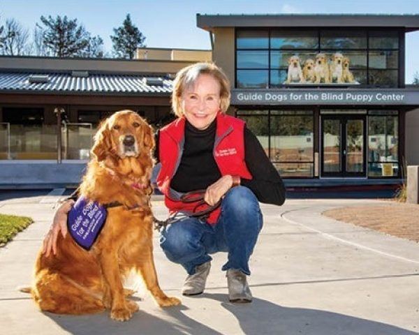 President and CEO of GDB and her Golden Retriever ambassador dog in front of the Puppy Center.