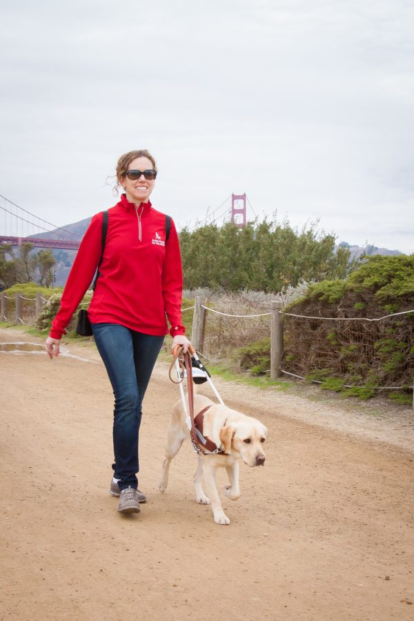 In this photo, Jane walks with her yellow Lab guide dog, Pilaf, along a coastal trail with the Golden Gate Bridge in the background. Jane smiles while looking forward and Pilaf looks focused on their destination.
