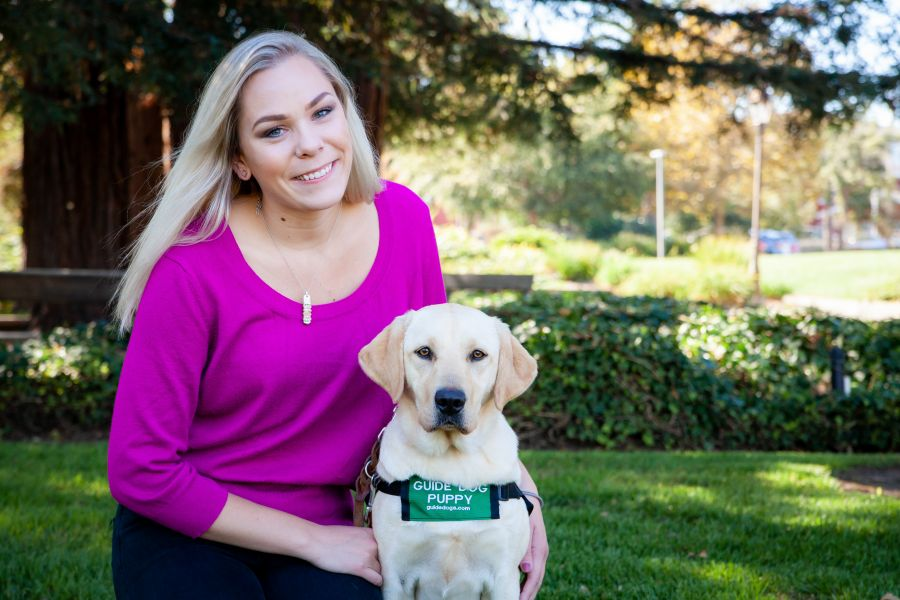 A photo of Alexandra kneeling on a green lawn next to a yellow Lab guide dog puppy. She is wearing a bright pink shirt and the puppy is wearing a green puppy-in-training jacket.