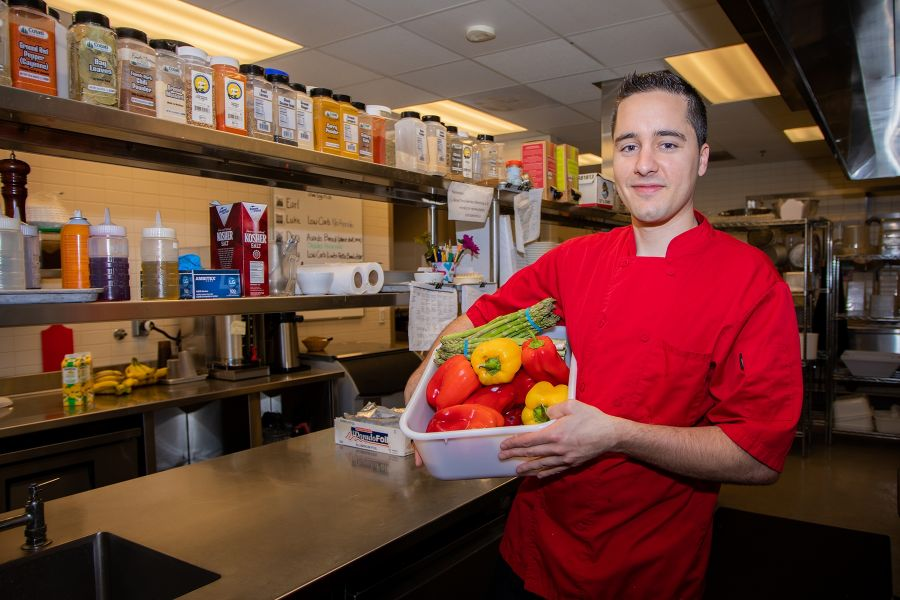 A portrait of Baptiste in the GDB kitchen holding a basket of fresh produce.