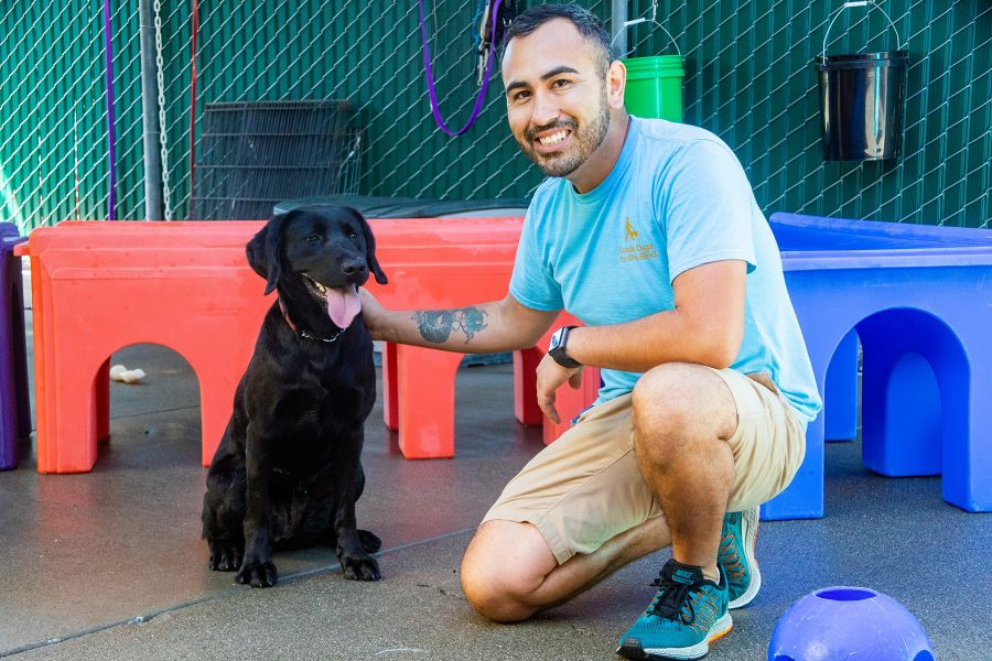 A portrait of Bobby with a black Lab in a dog play area full of colorful toys.