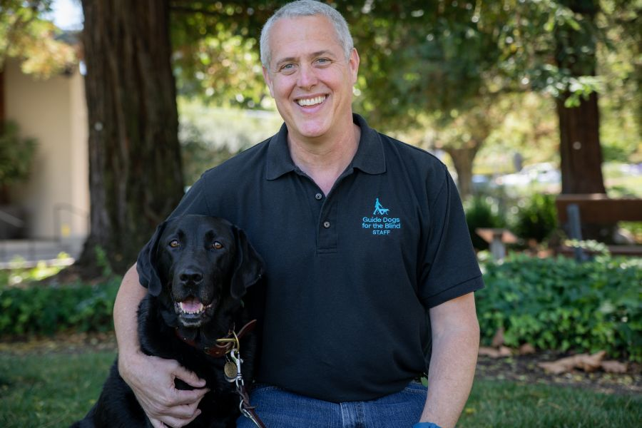 A portrait of Jim with a black Lab by his side.