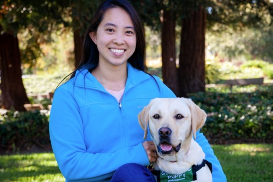 A portrait of Lynna with a yellow Lab guide dog puppy.