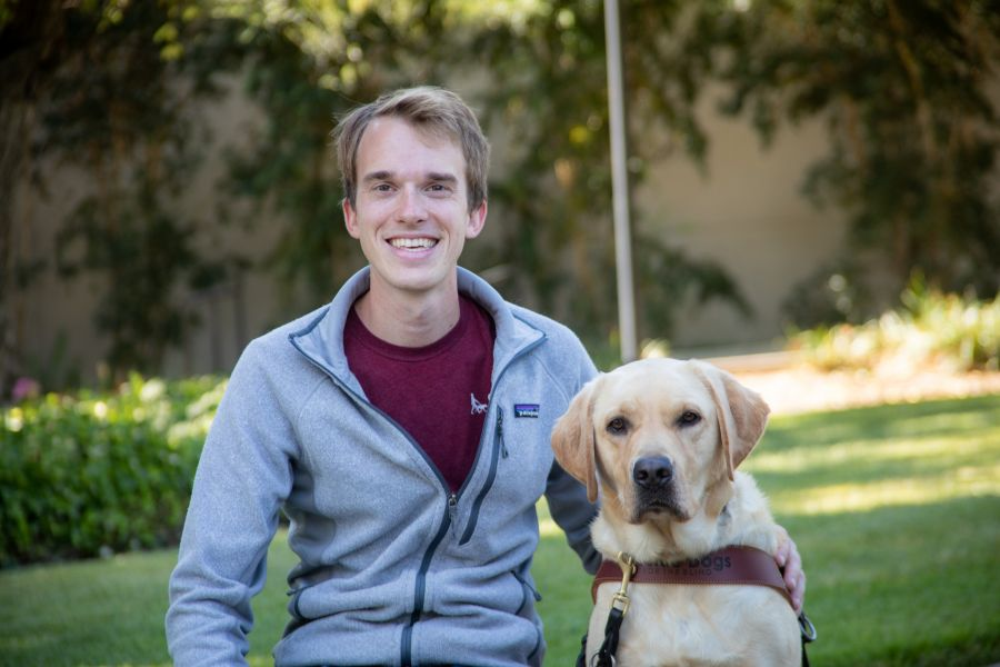 A portrait of Jack with a yellow Lab guide dog at his side.