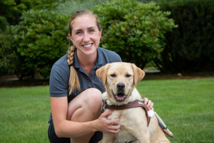 A portrait of Kate kneeling next to a yellow Lab guide dog.
