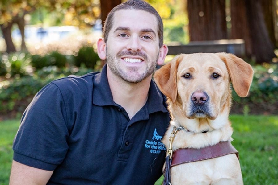 A portrait of Adam with a yellow Lab guide dog.