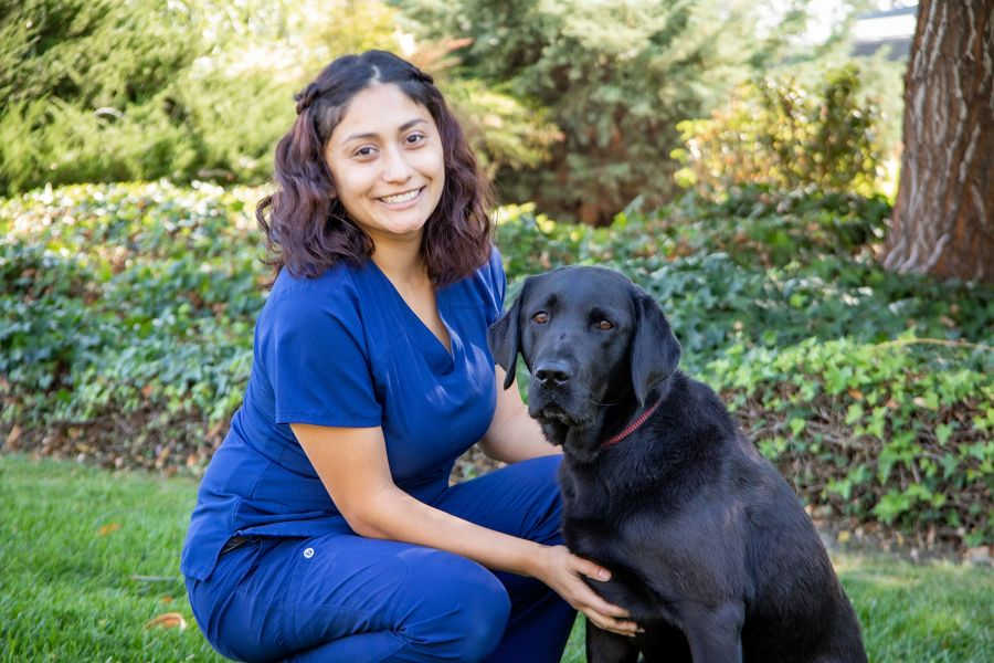 A portrait of Maribel with a black Lab against a backdrop of lush green landscaping.
