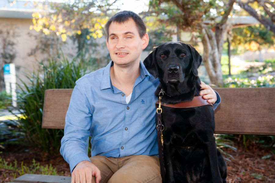 A portrait of Jake sitting on a bench next to his black Lab guide dog.