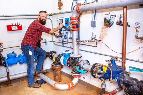 A man working on pipes inside of a large boiler control room.