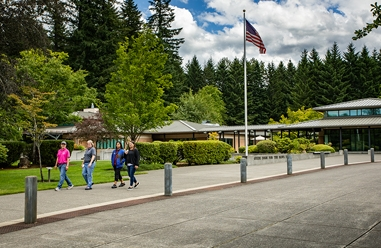 A photo of GDB's Oregon campus, showing a small group of people walking on a sidewalk, and the dormitory and visitor center in the background. There is a blue sky dotted with fluffy white clouds, and the lush campus grounds are green and full of trees.
