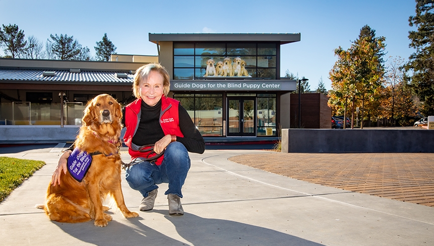 GDB CEO Christine Benninger with her Golden Retriever Theia. The Puppy Center is in the background.