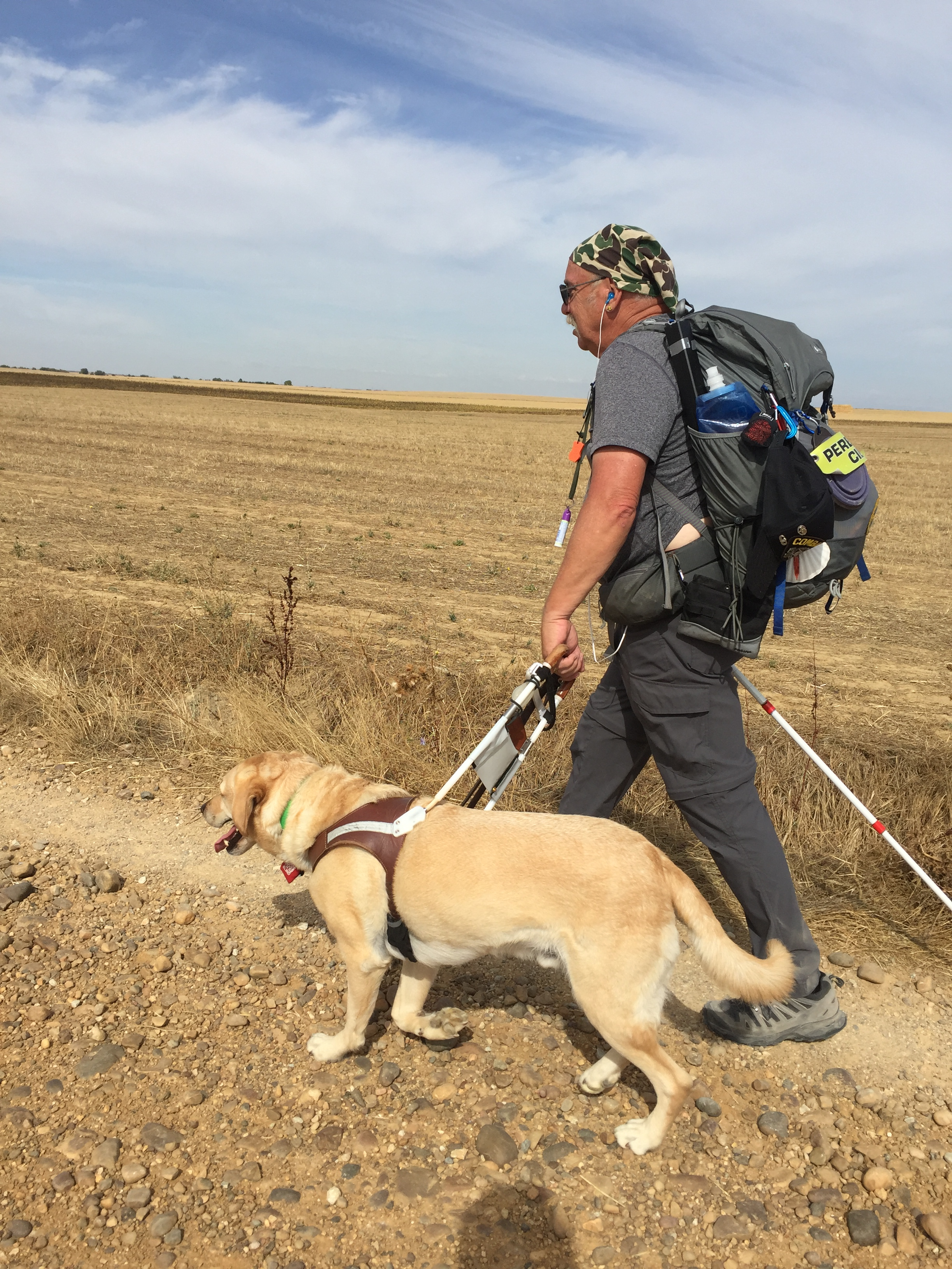 Phil (wearing a backpack) walks mid-stride with guide dog Jeff (yellow Lab) down a rocky path.