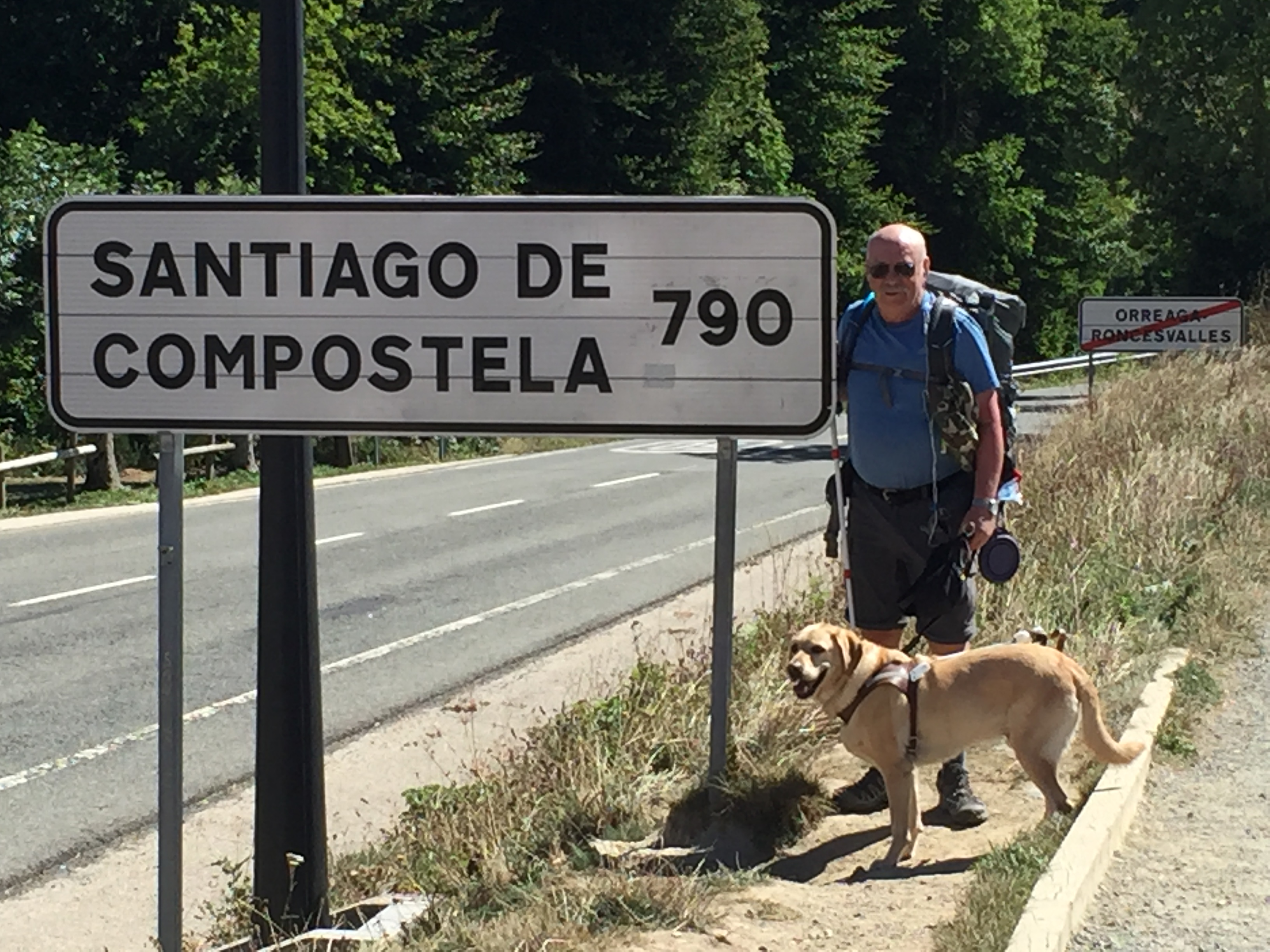 """Phil and his guide dog Jeff (yellow Lab) stop to pose next to a large sign that reads """"SANTIAGO DE COMPOSTELA 790"""""""