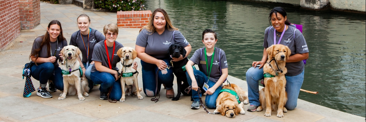 A group of six puppy raisers kneeling next to the guide dog puppies that they are raising.
