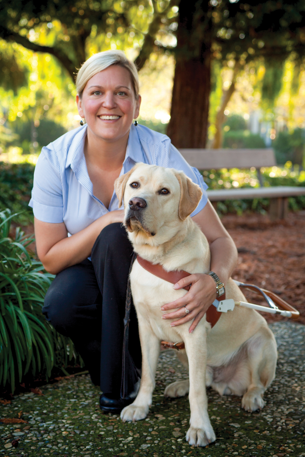 A portrait of Susan Armstrong sitting next to a yellow Lab guide dog.