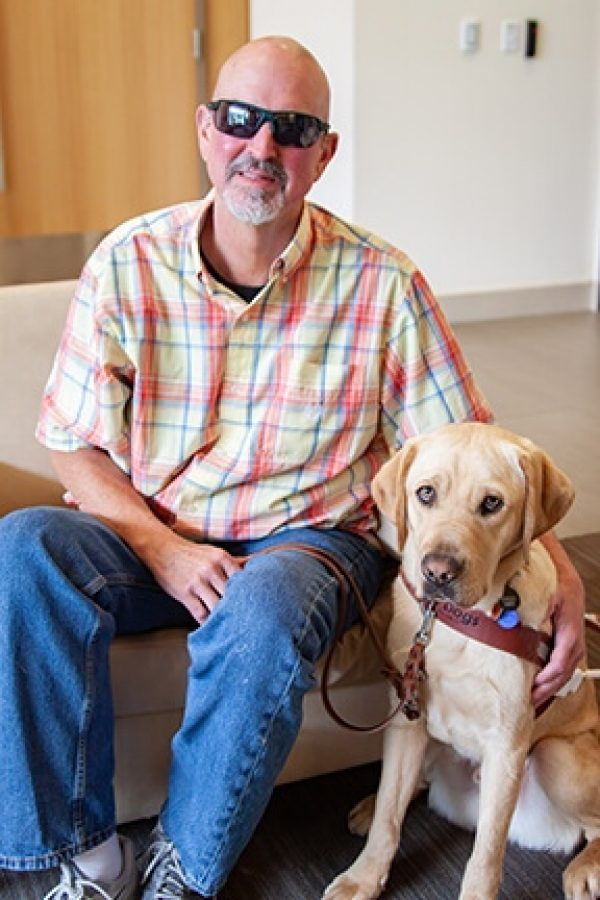 GDB graduate Barry Simmons with his guide dog, a yellow Lab named Virgo.