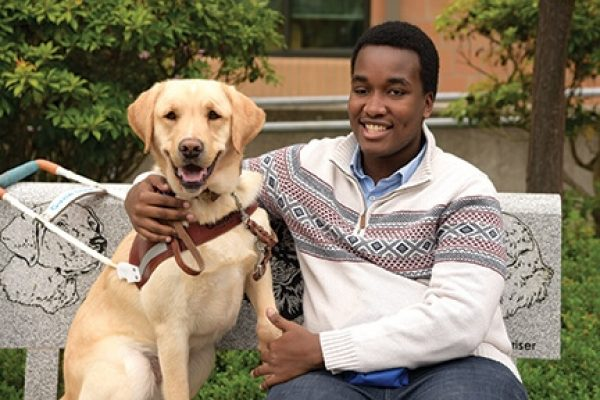 Brian and his yellow Lab Mannix sitting on a bench together.  Brian's arm is around Mannix, who is wearing his harness.