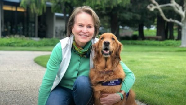 Guide Dogs for the Blind CEO Christine Benninger smiles at the camera while embracing her Golden Retriever, Theia.