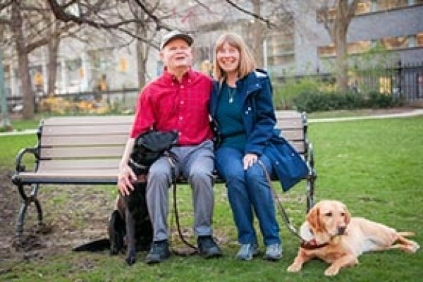 Denise and Chris Chamberlin with their guides dogs sitting on a park bench.