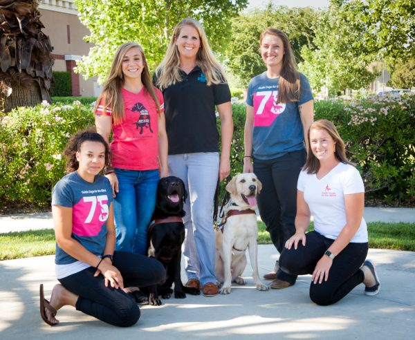 GDB's five new guide dog mobility instructors: Jessie St. Clair, Amanda Baumgartner, Palmer Dooley, Addie Yake, and Jane Allman, with two guide dogs in harness (one black Lab and one yellow Lab).