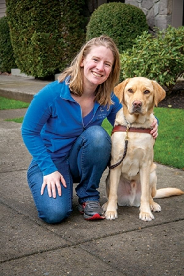 Guide Dog Mobility Instructor Jamie Mattison kneeling next to a yellow Lab guide dog in harness.