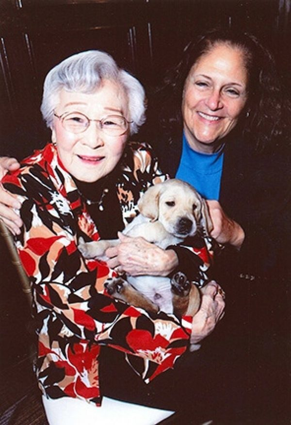Stella Westwood holding a baby yellow lab puppy, with her friend Janice Carter