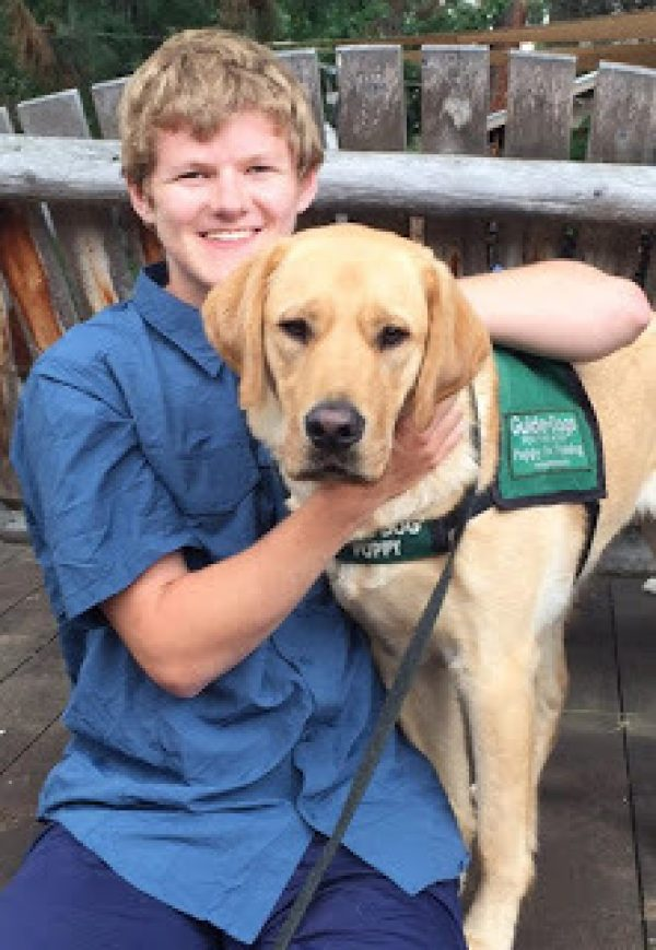 Sam Nelson with a yellow Lab guide dog puppy.