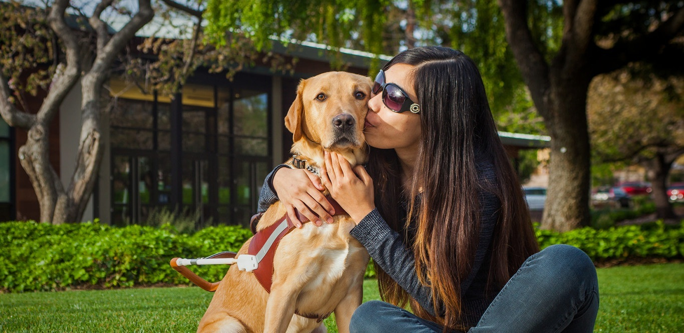 A female grad kisses her yellow Lab guide dog